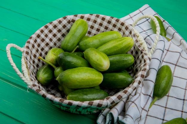 Widok z boku ogórków w koszu z innymi na tkaninie i zielonym stole