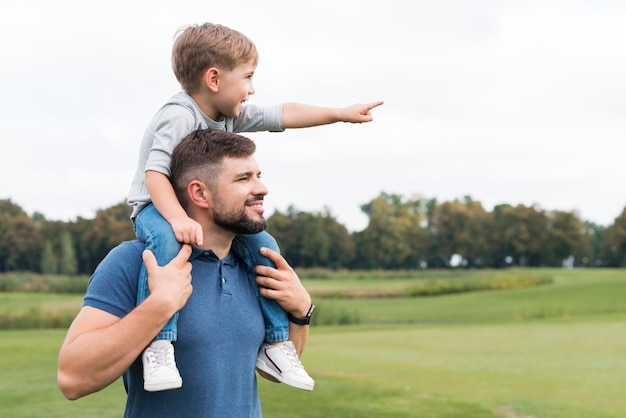 Widok z boku ojca trzymającego syna na ramionach