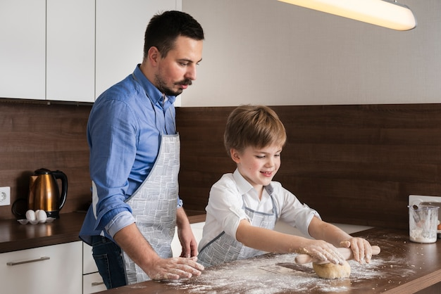 Widok z boku ojciec i syn toczenia ciasta