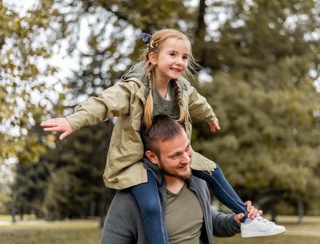 Widok Z Boku Ojciec Niosący Dziewczynę Na Ramionach Premium Zdjęcia