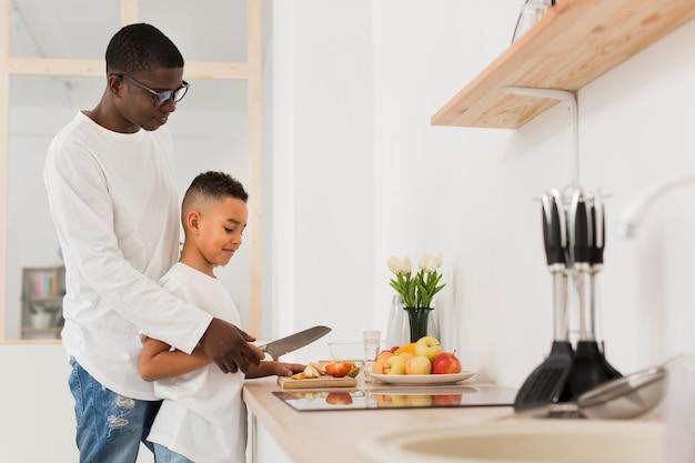 Widok z boku ojciec uczy syna do krojenia owoców