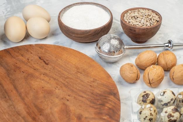 Widok z boku okrągłej drewnianej deski do krojenia owsa w brązowej misce jajka orzechów włoskich na lodowym tle