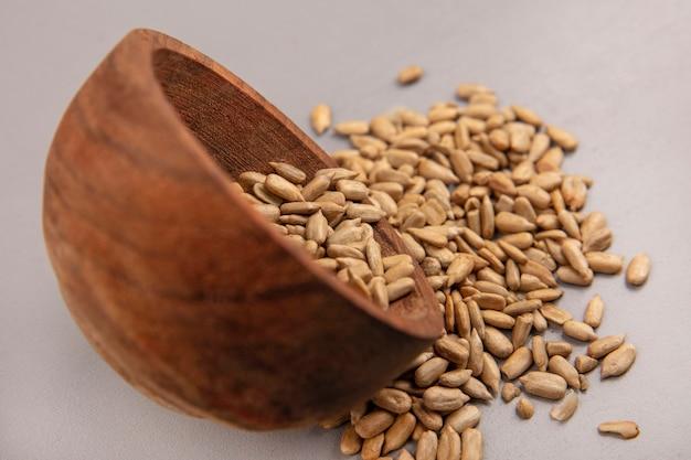 Widok z boku organicznych łuskanych nasion słonecznika wypadających z drewnianej miski na szarej ścianie