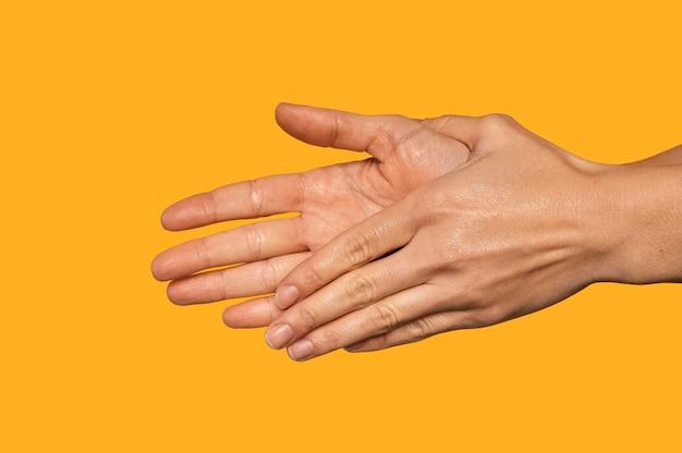 Widok z boku osoba mycie rąk na pomarańczowym tle