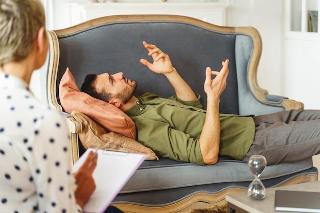 Widok Z Boku Pacjenta Płci Męskiej Wykonującego Gesty Rękami Podczas Sesji Terapeutycznej Premium Zdjęcia
