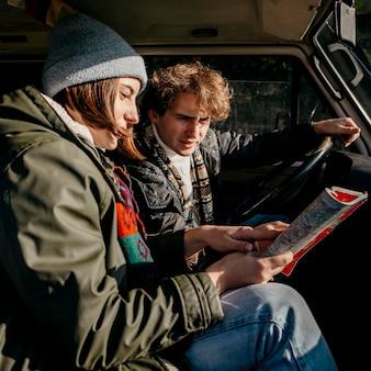 Widok z boku para patrząc na mapę podczas jazdy samochodem