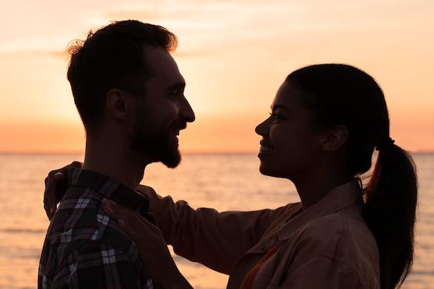 Widok z boku para patrząc na siebie o zachodzie słońca