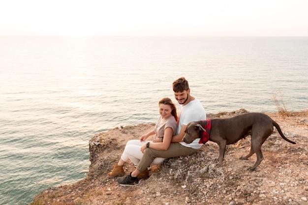 Widok z boku para siedzi obok swojego psa na wybrzeżu