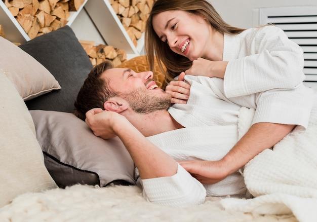 Widok z boku para w łóżku ubrana w szlafroki