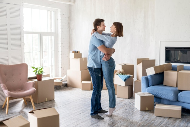 Widok z boku pary obejmującej się w domu wśród pudeł w dniu wyprowadzki