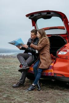 Widok z boku pary sprawdzającej mapę w bagażniku samochodu na zewnątrz