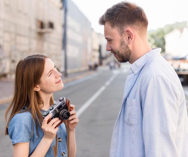 Widok z boku pary turystycznej na zewnątrz z aparatem