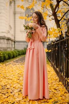 Widok z boku pełnej długości jednej pięknej zmysłowej młodej brunetki w różowej sukni ślubnej i stojącej w parku jesienią w pobliżu zabytkowej katedry i trzymającej bukiet ślubny, zdjęcie pionowe