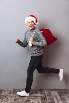 Widok z boku pełnej długości obraz szczęśliwego mężczyzny w swetrze i świątecznej czapce biegnącej trzymając torbę z prezentami i patrząc