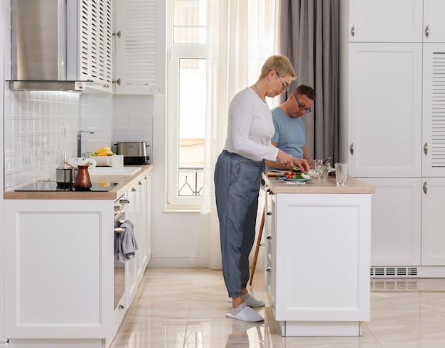 Widok z boku pełnej długości para starszych gotowania w kuchni portret szczęśliwej rodziny