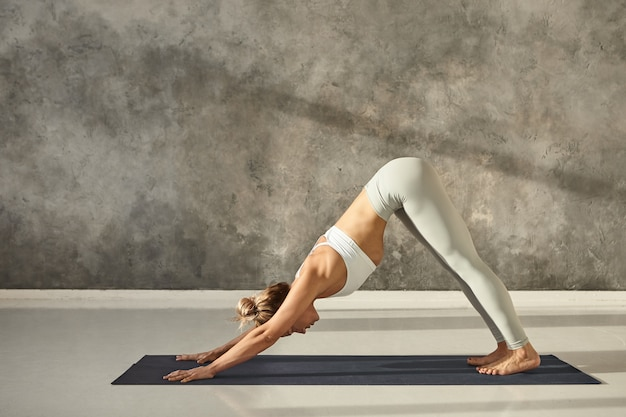 Widok z boku pełnej długości pięknej młodej kobiety w stroju sportowym, ćwiczącej w pomieszczeniu, ćwiczącej jogę na macie, wykonującej pozę psa skierowaną w dół lub pozę powitania słońca adho mukha svanasana