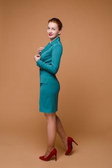 Widok z boku pełnej długości portret pięknej rudowłosej bizneswoman z czerwoną szminką, ubrana w szmaragdową suknię i czerwone szpilki. ona uśmiecha się do kamery trzymając ręce na sukience.