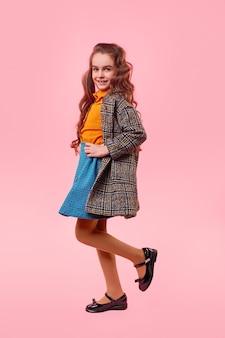 Widok z boku pełnej długości wesoła preteen dziewczyna ubrana w modny strój stojący na jednej nodze z rękami w talii i patrząc