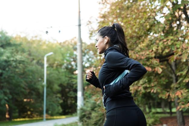 Widok z boku pewnej młodej kobiety fitness, jogging w parku, słuchanie muzyki przez słuchawki