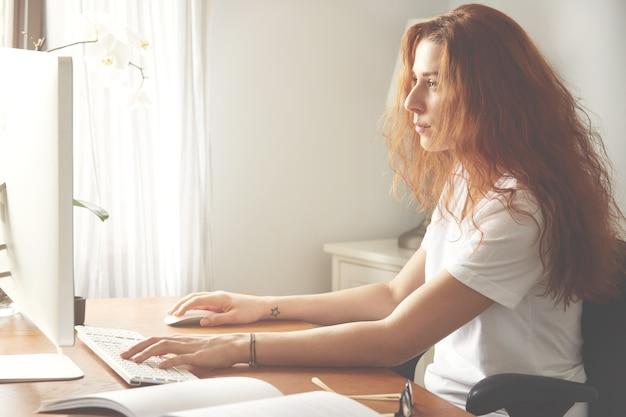 Widok z boku pewnej projektantki z luźnymi włosami, patrząc na ekran komputera