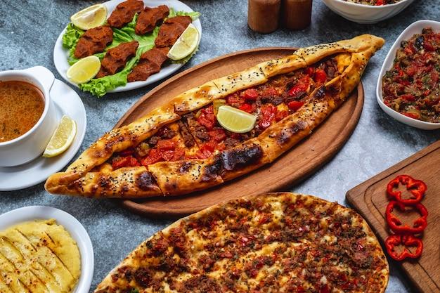 Widok z boku pide z mielonym mięsem, cebulą, ostrą papryką, plasterkiem cytryny i wegetariańskimi kulkami tatar na stole