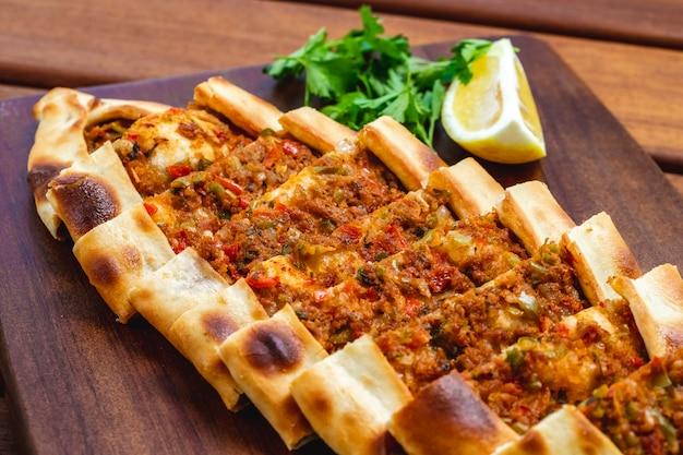 Widok z boku pide z mielonym mięsem, pomidorową cebulą, zielonymi pieprzem i plasterkiem cytryny na tacy