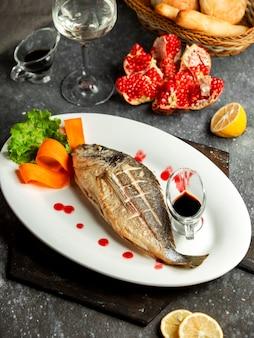 Widok z boku pieczonego okonia morskiego podany z sosem lemonnd narsharab na białym talerzu na czarno