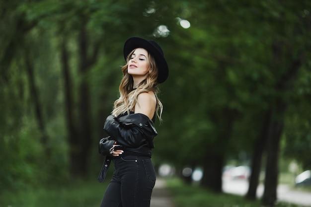 Widok z boku pięknej dziewczyny w skórzanej kurtce i czarnym kapeluszu, ciesząc się letni dzień na zielonej ulicy miasta.