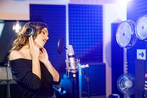 Widok z boku pięknej kobiety stojącej w studio ze słuchawkami i śpiewającej przed mikrofonem.
