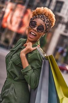 Widok z boku pięknej kobiety w okularach przeciwsłonecznych, trzymając torby na zakupy, patrząc na kamery i uśmiechając się na zewnątrz