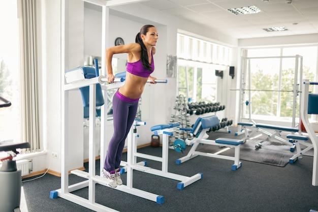 Widok z boku pięknej kobiety wysportowanej w odzieży sportowej przy użyciu wieży mocy w nowoczesnej siłowni.