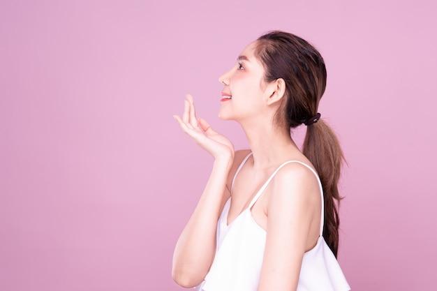 Widok z boku pięknej młodej azjatyckiej kobiety z czystą, świeżą, białą skórą delikatnie dotykającą własnej twarzy w pozie piękności.