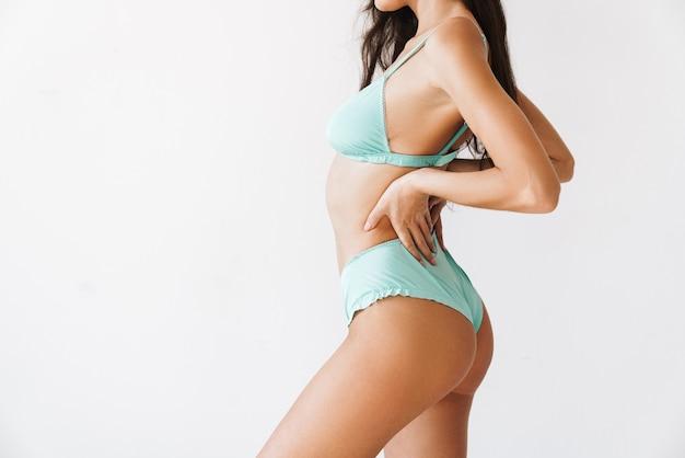 Widok z boku pięknej seksownej młodej szczupłej dziewczyny w bikini stojącej na białym tle nad białą ścianą, pozowanie