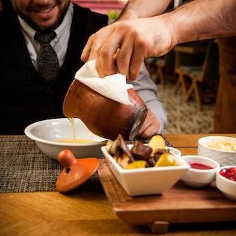 Widok z boku piti z głębokim talerzem, octem i człowiekiem w glinianym dzbanku na drewnianym stole