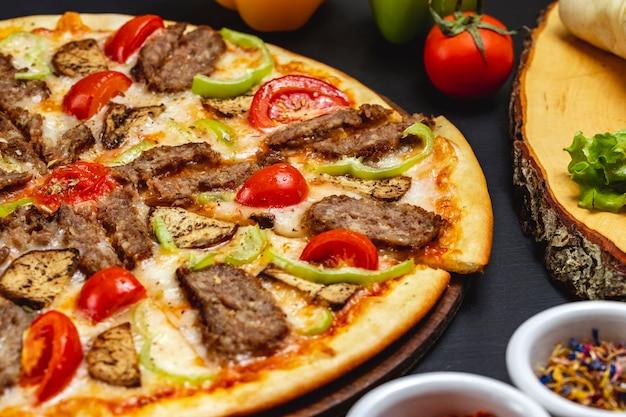 Widok z boku pizza z bakłażanem z grillowanymi plasterkami czerwonego mięsa, papryki i sera na stole
