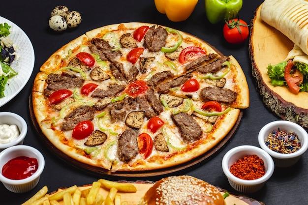 Widok z boku pizza z bakłażanem z grillowanymi plasterkami czerwonego mięsa, pomidora, sera i bakłażana na stole