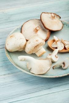 Widok z boku płyty z całymi świeżymi grzybami na rustykalnej drewnianej powierzchni