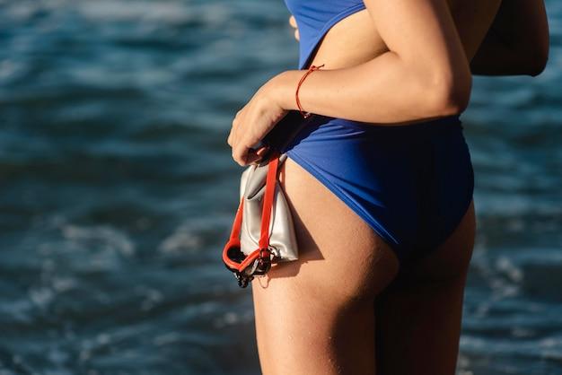Widok z boku pływaczka trzymając okulary pływackie i czapkę