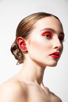 Widok z boku pogodnej modelki z czerwonymi ustami i cieniami do powiek stojącej z pomalowanym uchem na białym tle w studio