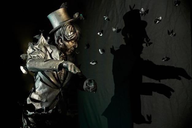 Widok z boku pokazującego ekspresyjne emocje profesjonalnego mima, ubranego jak posąg z brązu z mnóstwem sztucznych motyli, które wydają się ciągnąć go do garnituru i kapelusza.