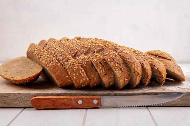 Widok z boku pokrojone brązowy kaczan obsianych na deskę do krojenia i nóż na powierzchni drewnianych i białym tle