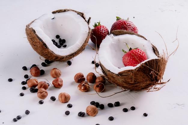 Widok z boku pokrojone nasiona kokosa i orzechów czarnego pieprzu z truskawkami na białym stole