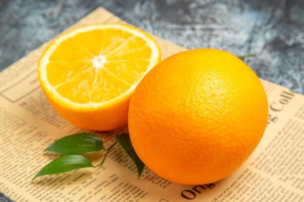 Widok z boku pokrojonej na pół i całej świeżej pomarańczy z liśćmi na gazecie na szarym tle