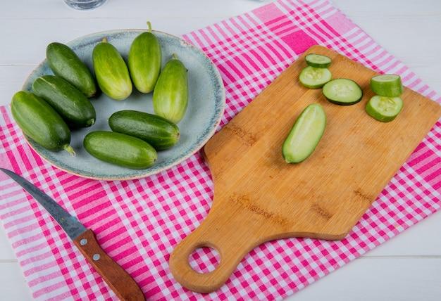 Widok z boku pokrojonych i pokrojonych ogórków na desce do krojenia z całymi w talerzu i nożem na kratce i drewnianym stole