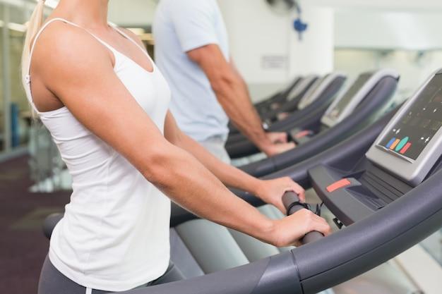 Widok z boku połowie sekcji para działa na bieżnie w siłowni