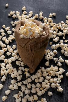 Widok z boku popcornu w torbie wory na czarnym pionie