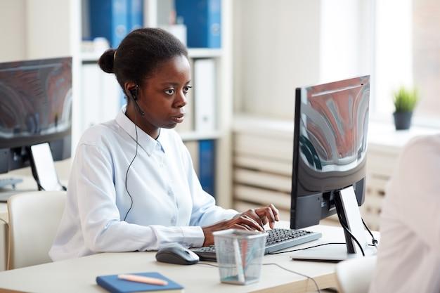 Widok z boku portret african-american kobiety noszenia zestawu słuchawkowego i korzystania z laptopa podczas pracy nad obsługą klienta