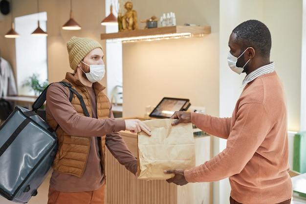 Widok z boku portret afro-amerykańskiego mężczyzny, przekazanie zamówienia do dostawy człowiekowi w kawiarni, obaj noszący maski, covid koncepcja, kopia przestrzeń