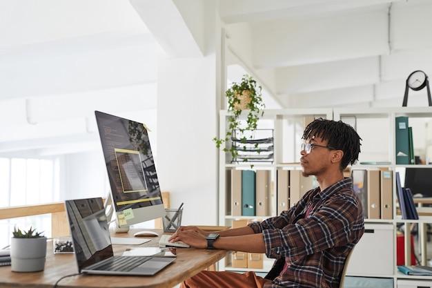 Widok z boku portret afroamerykańskiego programisty it piszącego na klawiaturze z czarno-pomarańczowym kodem programowania na ekranie komputera i laptopie we współczesnym wnętrzu biurowym, kopia przestrzeń