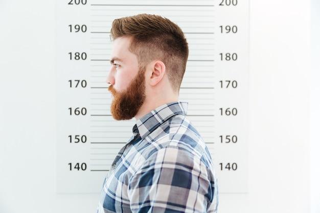 Widok z boku portret arested mężczyzny stojącego na ścianie miarowej